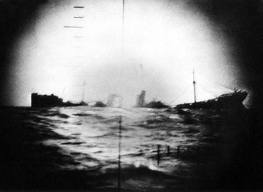 A Japanese merchantman, its keel broken by an American torpedo, breaks up before sinking.