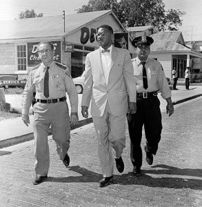 Dr. Gilbert R. Mason, Sr. is led to the courthouse by Biloxi police officers